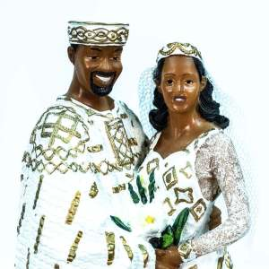 wedding couple figurine, in royal gold african attire, closeup