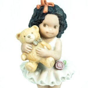 figurine, little girl holding teddy bear, closeup