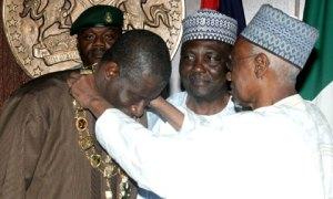 Shehu Shagari decorating current President, Goodluck Jonathan with Nigeria's highest honour, the Grand Commander of the Federal Republic, GCFR.
