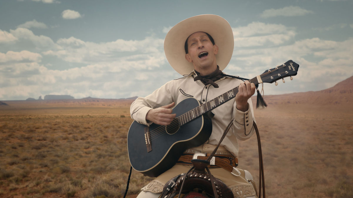 Buster Scruggs, a dandy gunslinger, playing the guitar on horseback.
