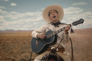 Buster Scruggs, a dandy gunslinger, playing the guitar on horseback.
