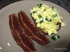 Scrambled eggs with spinach on rye bread and turkey bacon.
