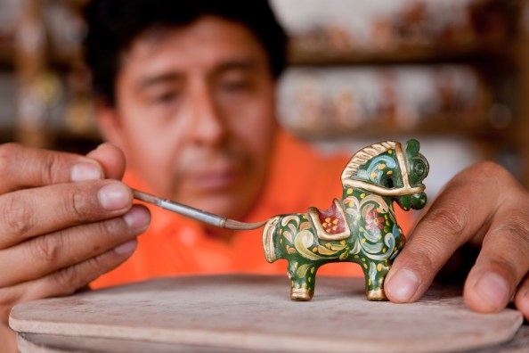 An Ayacucho artist painting a horse figurine | Photo by Alex Bryce / PromPerú | All rights reserved by SmithsonianNMAI