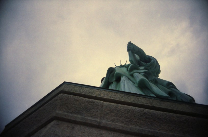 A view of the Statue of Liberty from below, against a cloudy sky