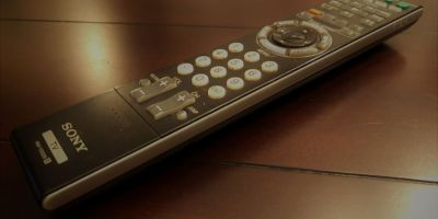 A remote control sits on a wooden surface
