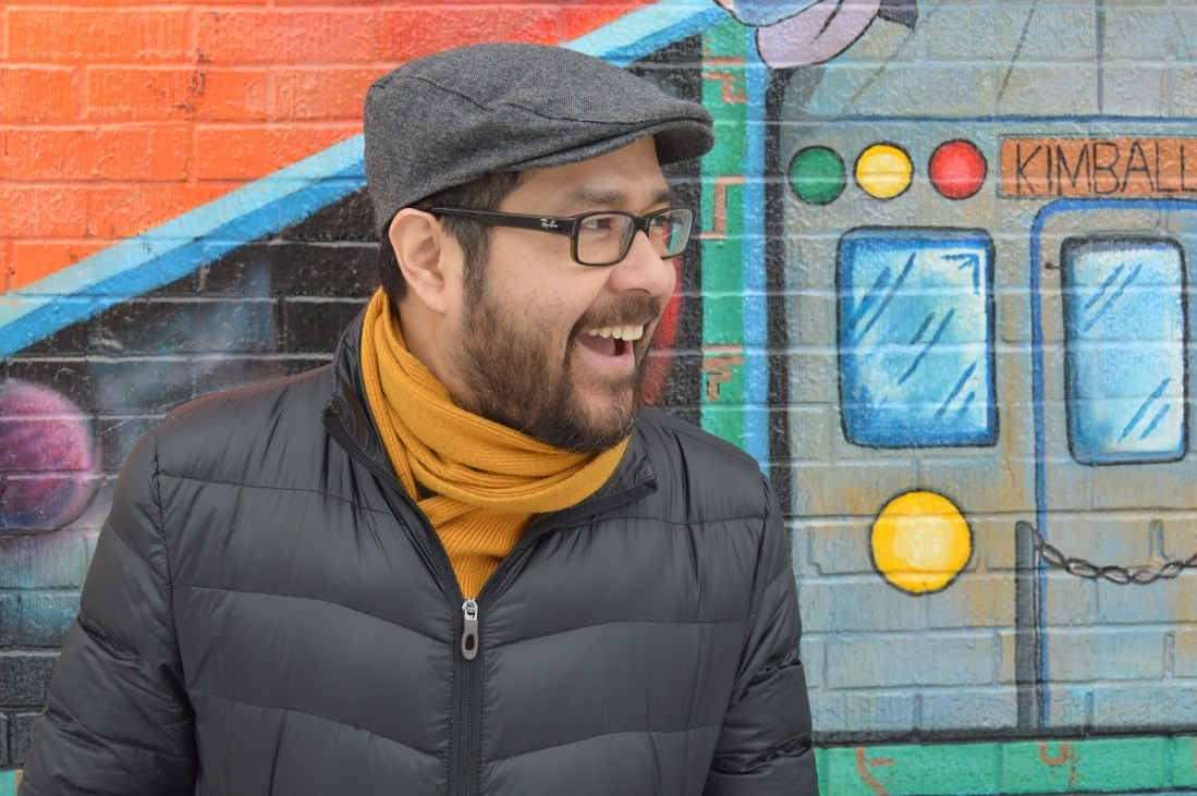 Jose Oliva in front of a mural with a happy, laughing expression