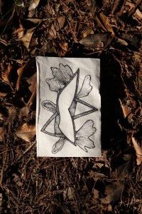 a canvas featuring a geometric image with leaf forms lies on the ground, which is covered with sticks and dead leaves