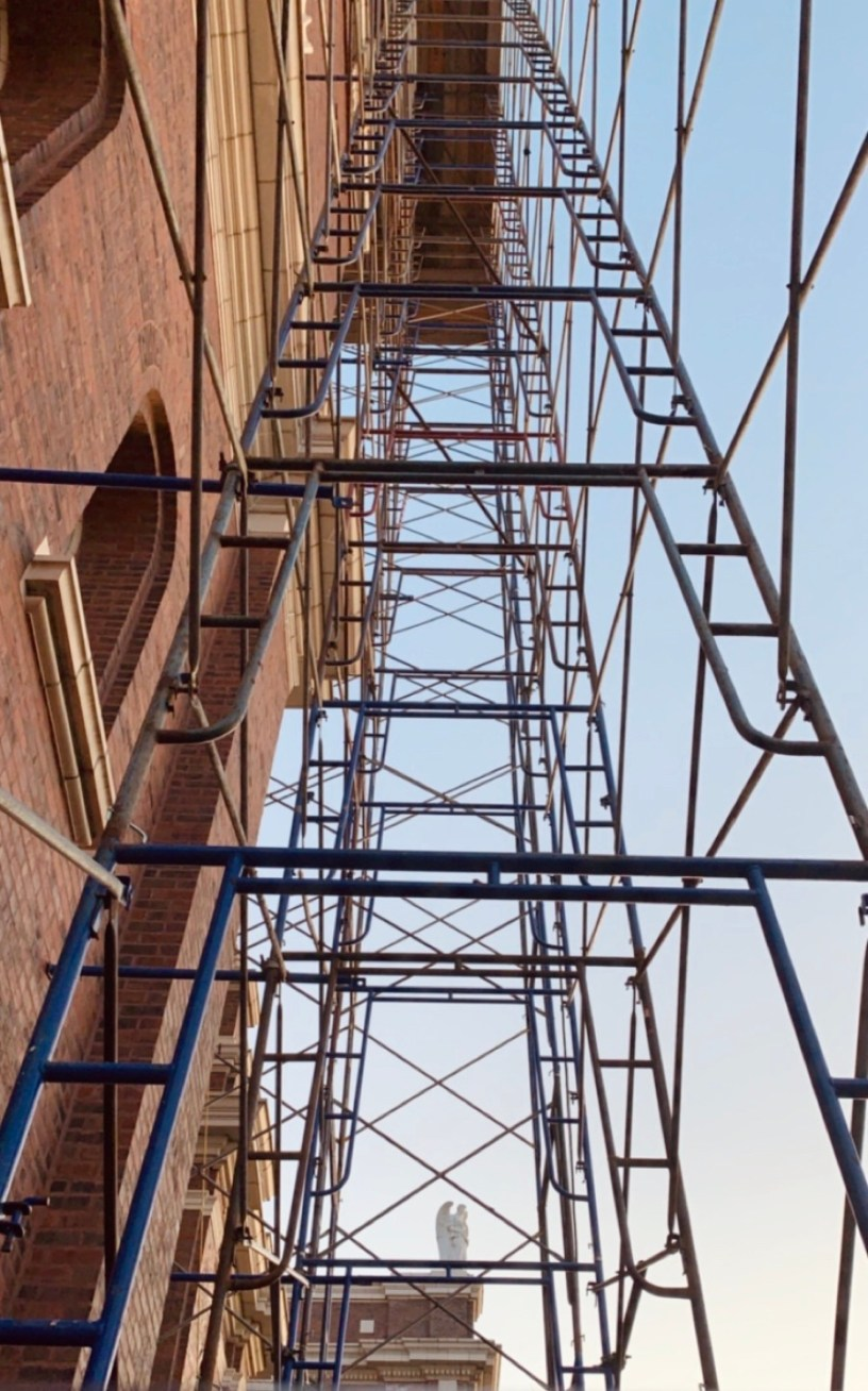 photograph looking upwards at metal scaffolding against the side of a brick building