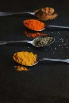 A photo of brown, red, green and yellow Cooking Spices in teaspoons on a black background
