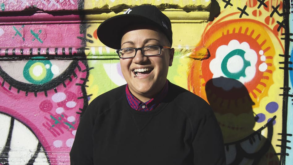 Photo taken of writer Gabby Rivera. She is smiling with a glasses and a black cap.