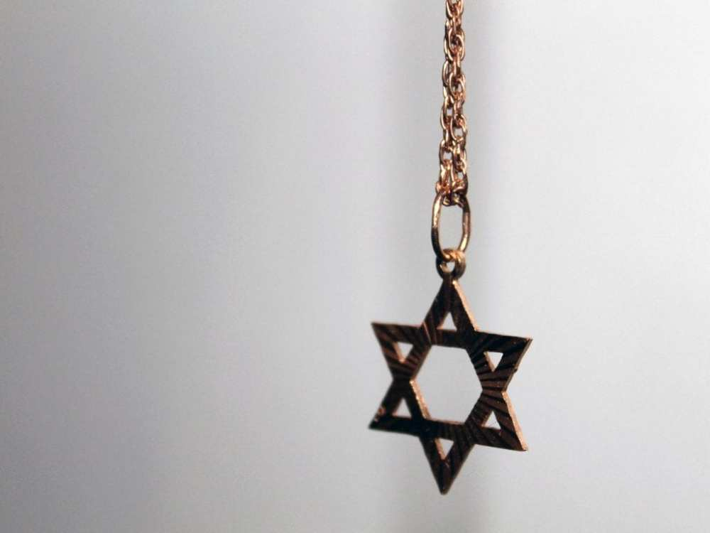 The image shows a Star of David pendant on a chain necklace.