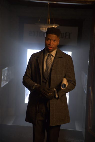 Actor London Brown as David in Tales From the Hood 3, wearing a business suit and overcoat, walking down a dark hallway