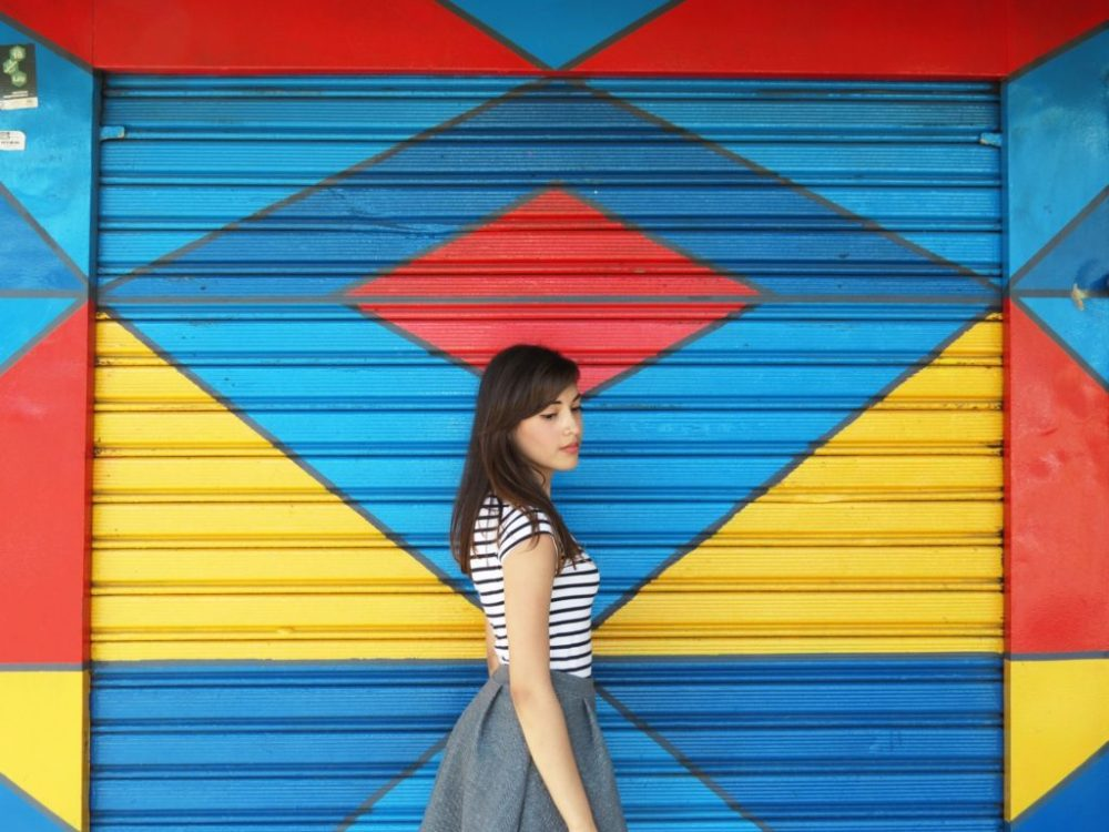 Girl stands in front of a brightly colored blue, red and yellow painted rolling commercial garage door.