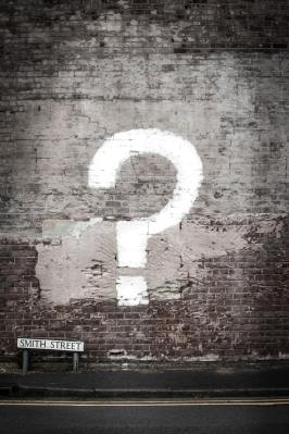 Image is of a brick wall with a question mark on it, symbolizing the questions in the discussion aspect.