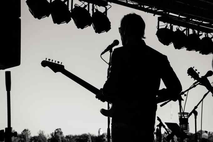 Guitarists, silhouette photo of man holding guitar