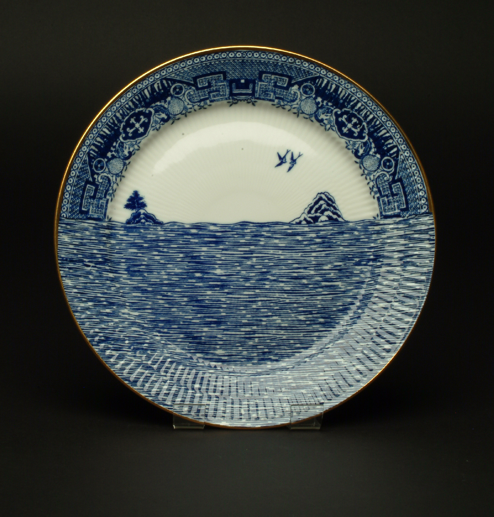 Plate from Scott's Cumbrian Blue(s), Cockle Pickers Willow tea set. Inglaze decal collages on Royal Copenhagen plate with gold lustre.