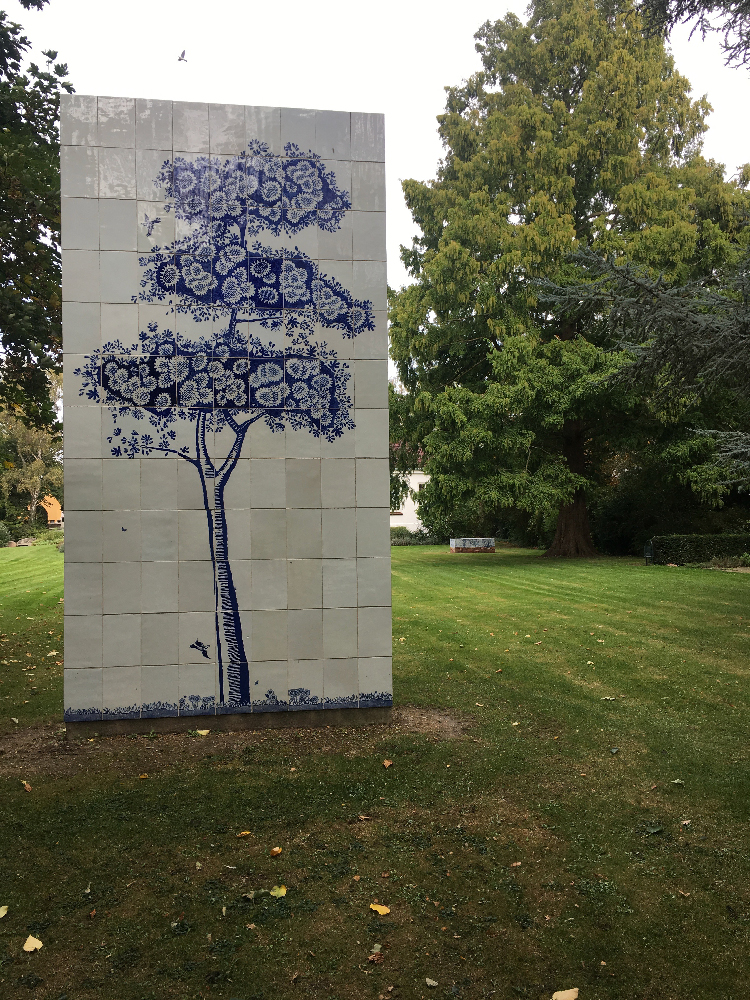 ''Scott's Cumbrian Blue(s), Guldagergård Tree (After Spode)' with 'Scott's Cumbrian Blue(s), A Flowerbed for Alice' in the background ….Tree: Inglaze decal collage, porcelain tiles on concrete form, 2450cm 4855cm, Paul Scott 2013. Flowerbed: porcelain tiles on a bed of bricks by Lillemor Petersson. Guldagergård, Skælskør Bygarden, Denmark, 203cm x 90cm x 70cm. Paul Scott and Lillemor Petersson 2016.