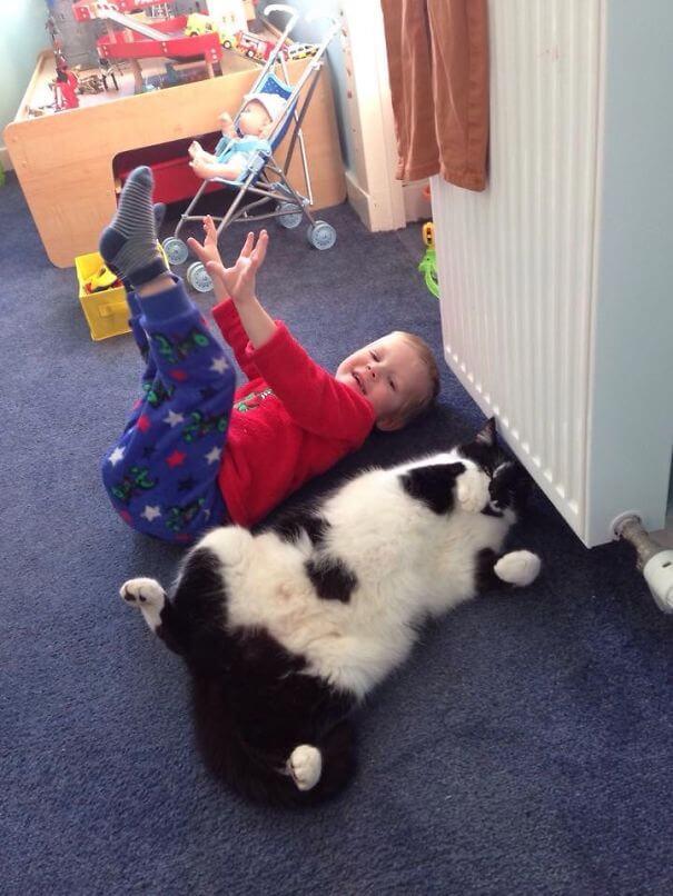 copil-care-se joaca-cu-pisica