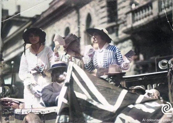 A computer colourised photo (originally black and white) from South Australia showing three women standing at the back of an open-top car. In the foreground is a Union Jack flag, which the computer algorithm has not recognised or coloured.