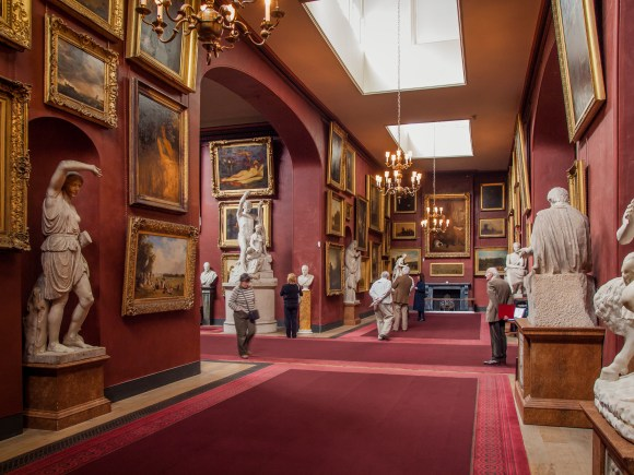 Photograph of a pinky red grand gallery with many paintings and gilt frames and marble sculptures.