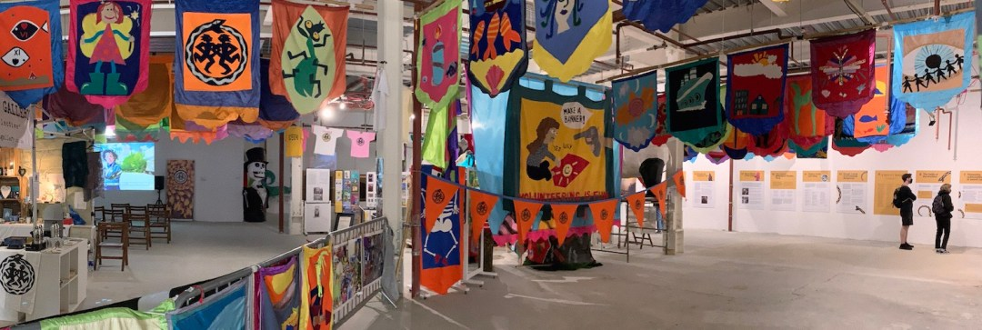 A wide image showing the Golowan exhibition from the entrance. Colourful banners hang from the ceiling, and from the sides of a central wall. Printed panels can be seen fixed to the walls on the right, being browsed by a couple of visitors.