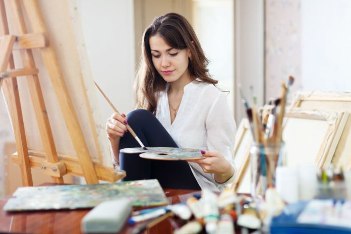 28020484 - long-haired beautiful artist paints on canvas in workshop