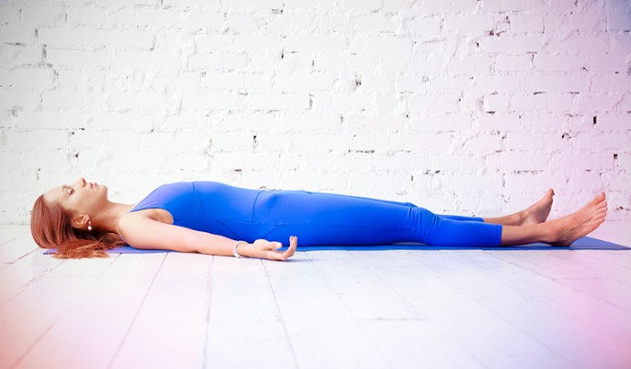 A woman in the Supported Corpse pose.