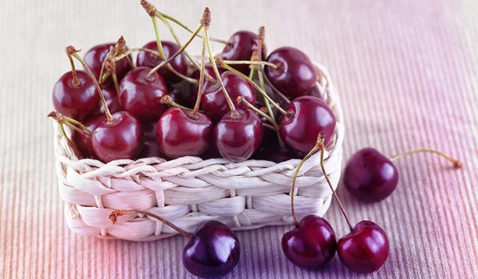 Crimson red cherries with their stems intact are perfect to eat