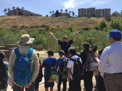 Eric Strauss speaking to local students near the Ballona Wetlands with his hands raised in the air