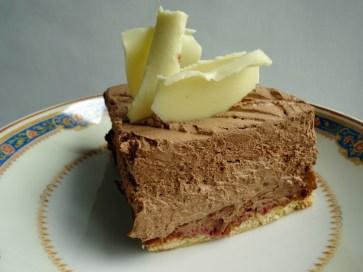 Génoise imbibée de griottes au sirop, recouvert d'un croquant au spéculos, puis nappé d'une mousse chocolat/praliné.
