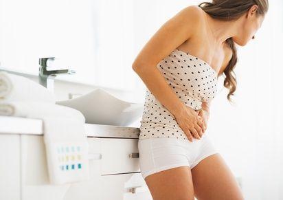 Woman having stomachache in bathroom