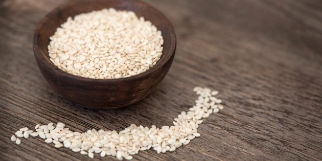 A samll wooden bowl filled with calcium rich sesame seeds