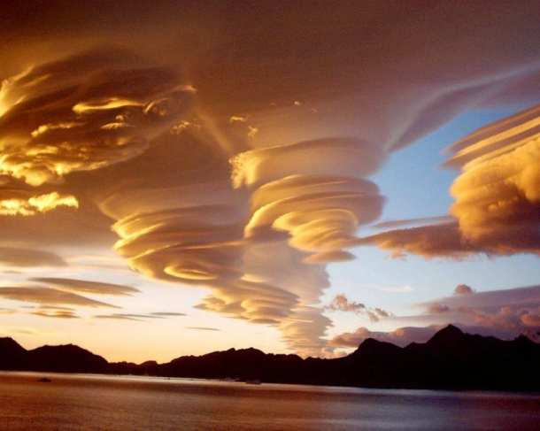 Small lenticular cloud formations that look like UFOs over a lake at dusk