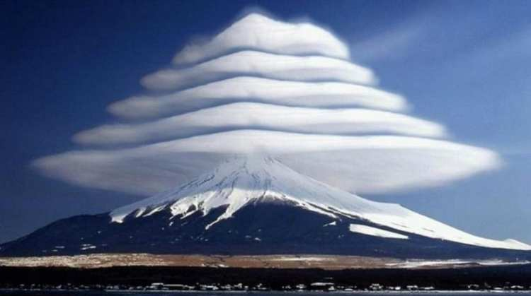 five layers of lens shaped lenticular clouds over a snowy mountain top