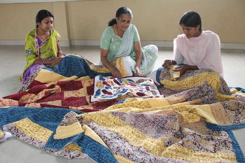 Women turning told sarees into quilts