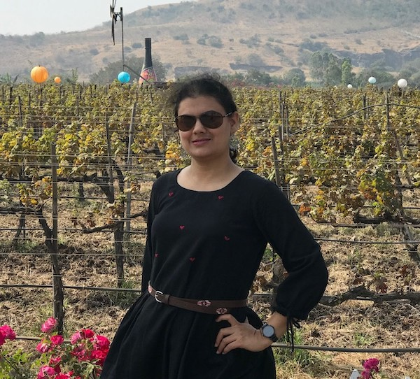 Ketki stands in front of vineyards