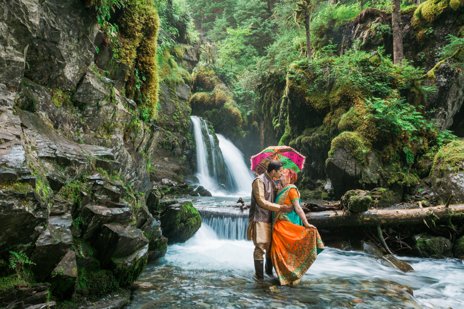 couple embracing in Indian clothing under a waterfall