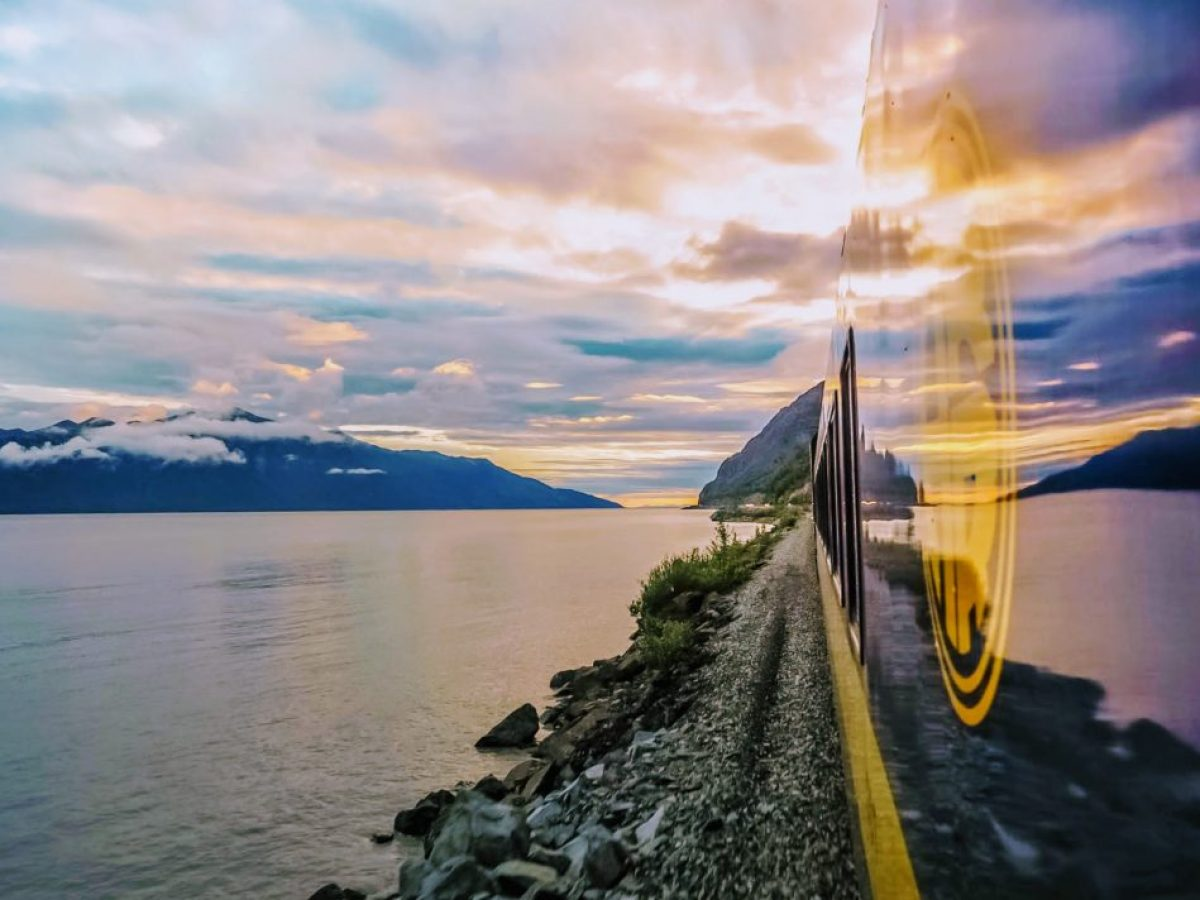 Alaska Railroad train riding into a vibrant sunset