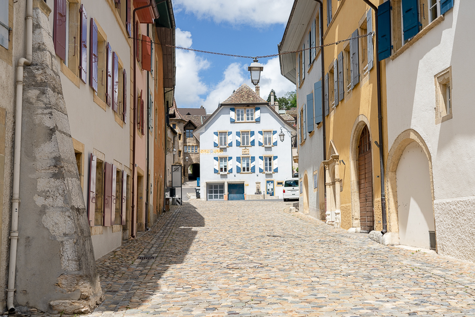 Cobblestone road in Switzerland with a historic european white and blue house at the end of the road