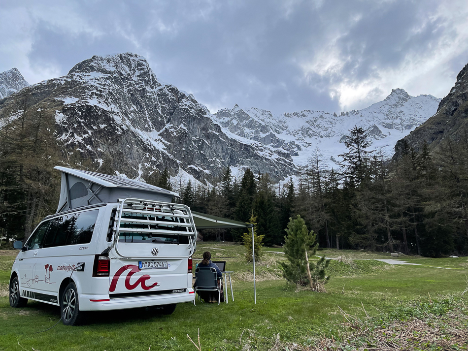 VW Campervan set up with a girl working outside below glaciers in Switzerland