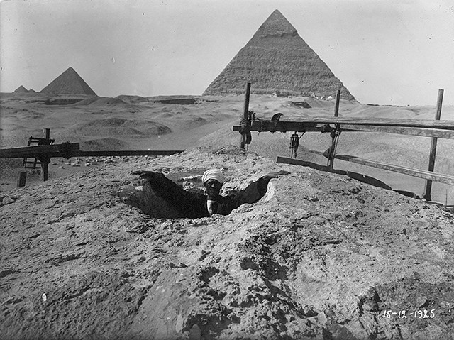 A man standing in a cavity at the head of the Great Sphinx.