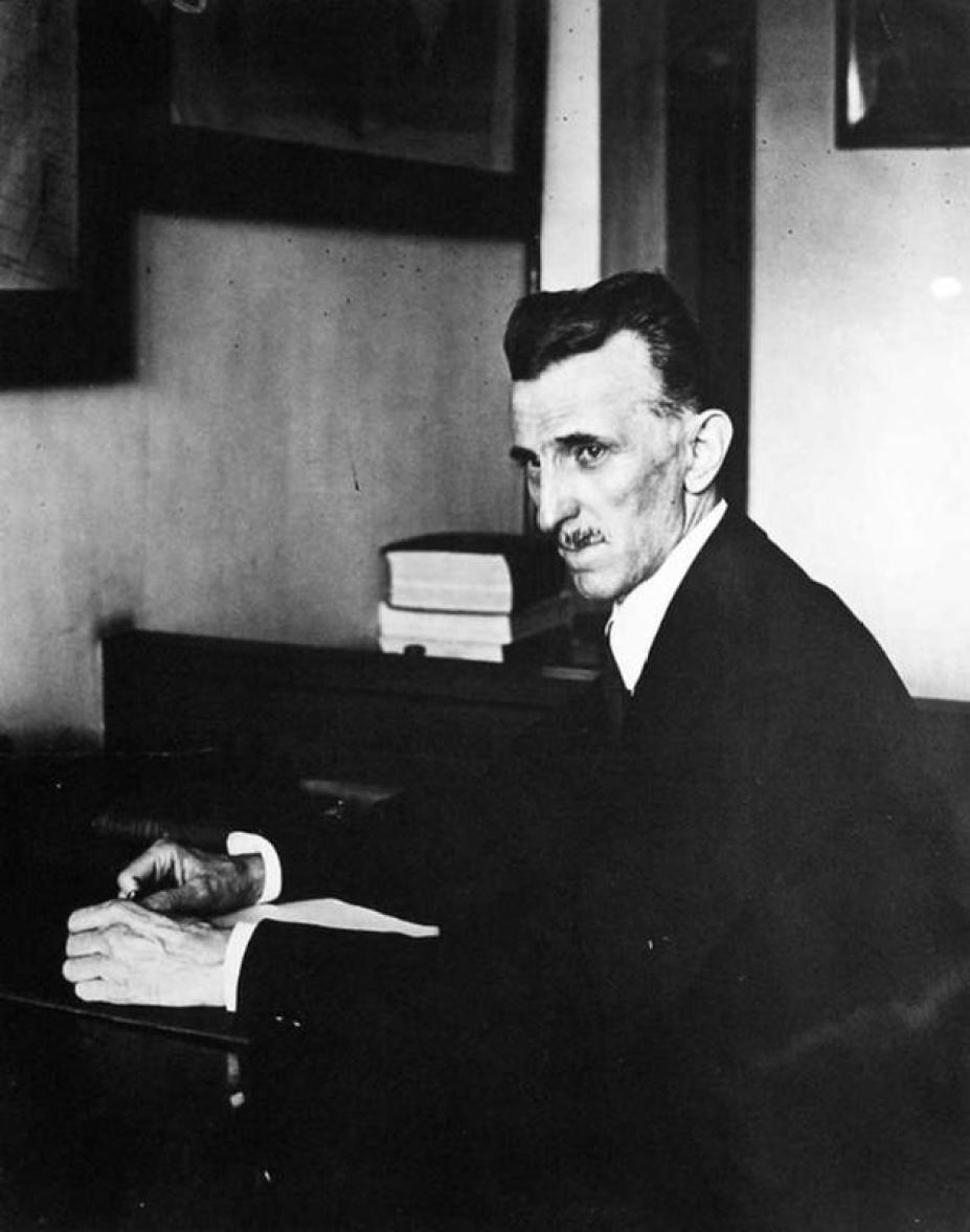 A photograph of Nikola Tesla working in his office in 1916.