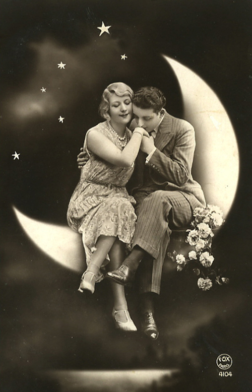 Couple sitting on the moon; man giving lady a hand kiss