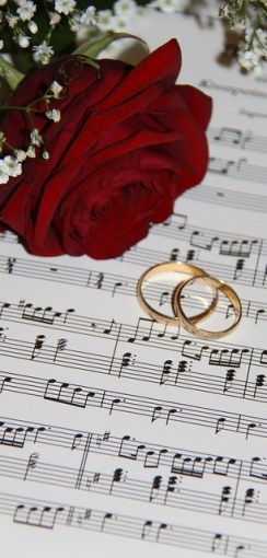 A red rose and two wedding rings on a sheet of music