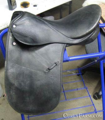 Photo of an older model Courbette Dekunffy Dressage Saddle on a blue saddle rack.