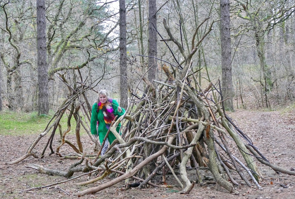 Woman poses in forest next to piles of branches |curlytraveller.com