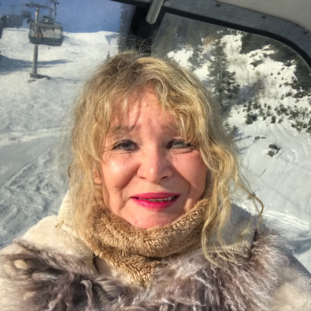 Woman enjoying the sun in a cable car in St. Anton  curlytraveller.com