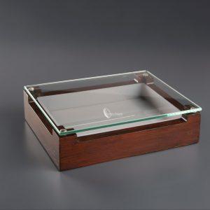 Caja de presentación con cristal modelo kiatos 25x18x7 cm. Este producto con cristal es perfecto para presentaciones. Está hecha en madera especial y cristal su forma es distinta hasta ahora, dando un toque de antigüedad basándose en el bosque. Las medidas son perfecta 25x18 parecidas a los platos normales para comensales. La caja tiene un tratado especial que resiste casi todo tipo de productos igual que su cristal. Con esta caja se pueda presentar con CO2, nitrógenohttps://es.wikipedia.org/wiki/Nitr%C3%B3geno Hacer simplemente unas espumas. Las presentaciones son a cargo de los chef, pero es un modelo que cualquier restaurante de categoría debería tener. Tenemos un taller especializado, podemos hacer una medida, o una idea, le haremos un presupuesto. Es fácil de lavar y no da ningún tipo de problemas por sus tratamientos. Al ser rectas son fáciles de apilar y si el problema de rupturas solo caería a cuenta de la ruptura del cristal. La fabricación de este producto varía entre una y dos semanas.