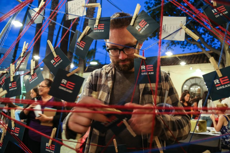 A man attaches his card to a giant dream-catcher at a PBS SoCal Re:Dream event. (Photo: Heather Toner)
