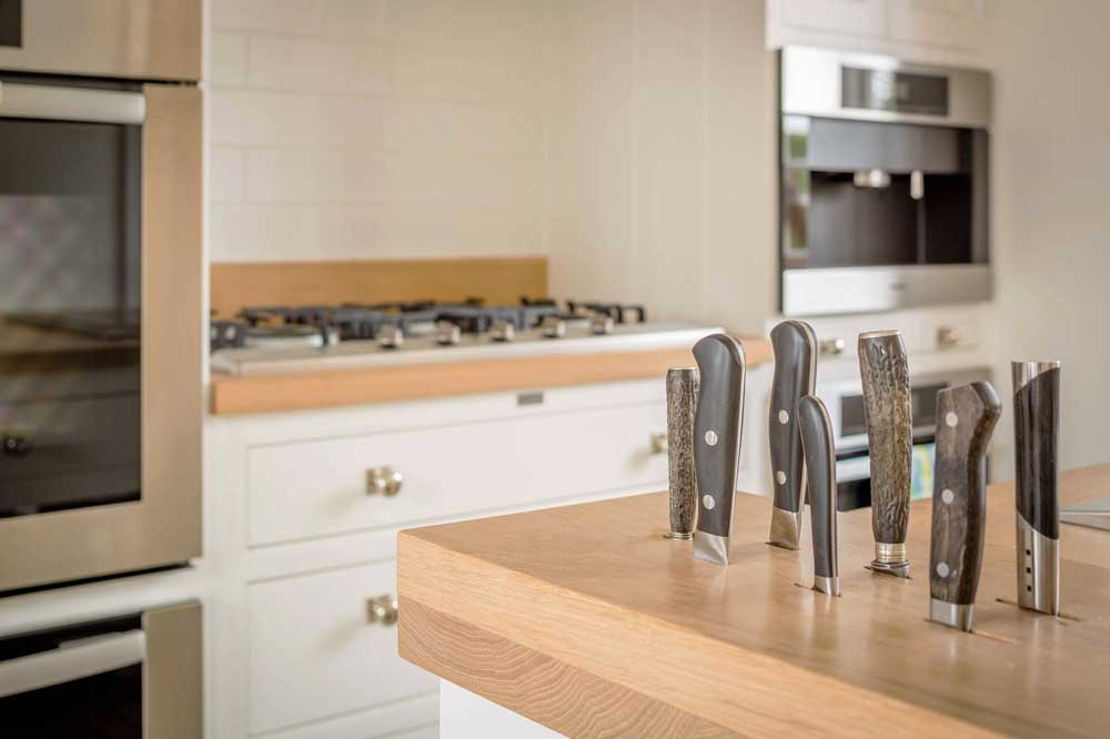 kitchen island doubles as a storage area for slotted knives